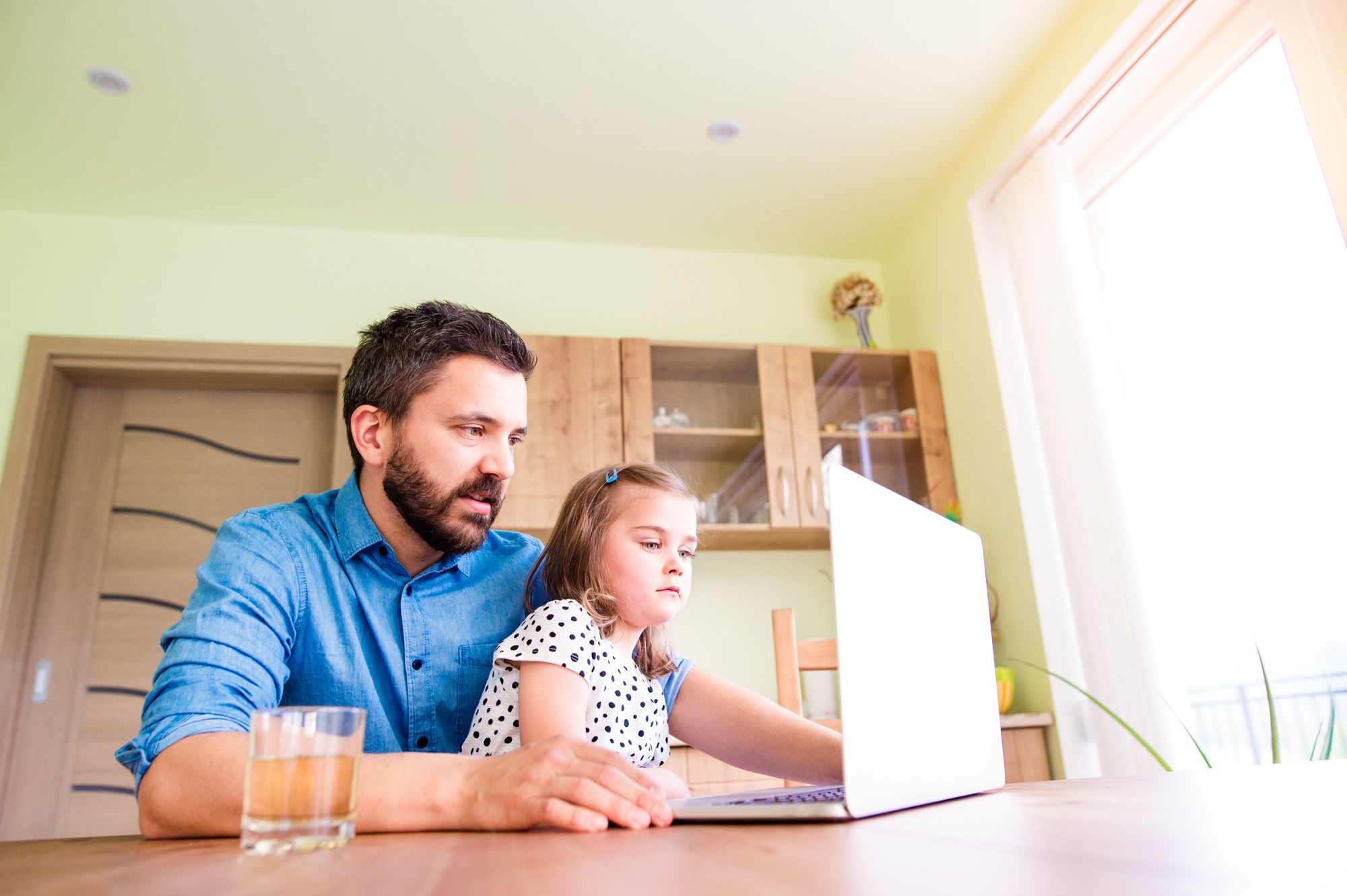 A father and daughter take an online class together while sitting at their kitchen table